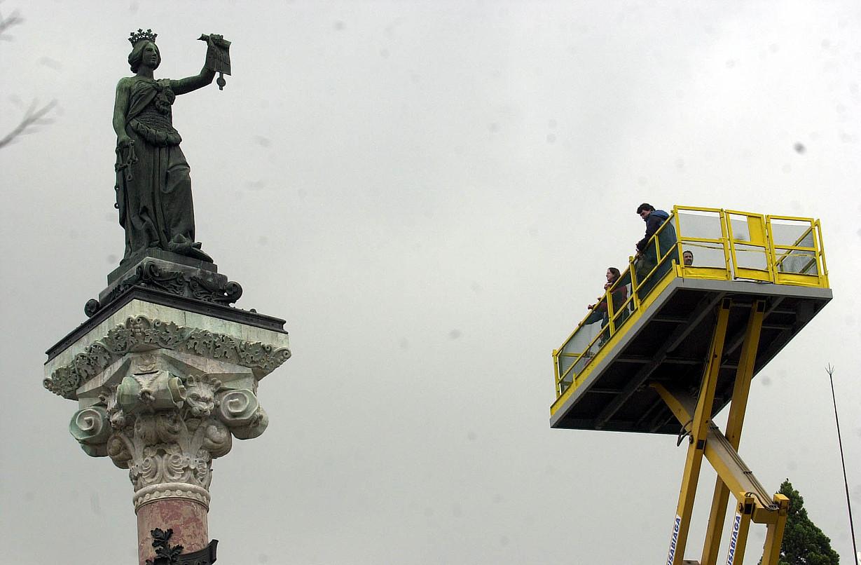 Herritar batzuk —alboko orrian— Nafarroako foruen estatua ikusten, igogailu batetik, 2003. urtean eginiko erakusketa baten harira. ©LANDER FERNANDEZ DE ARROIABE / FOKU