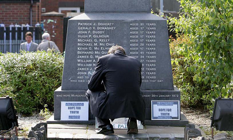 Gizon bat Bloody Sundayn hil zituztenen omenezko eskulturaren aurrean, Derryn, artxiboko irudi batean. ©STRINGER / EFE