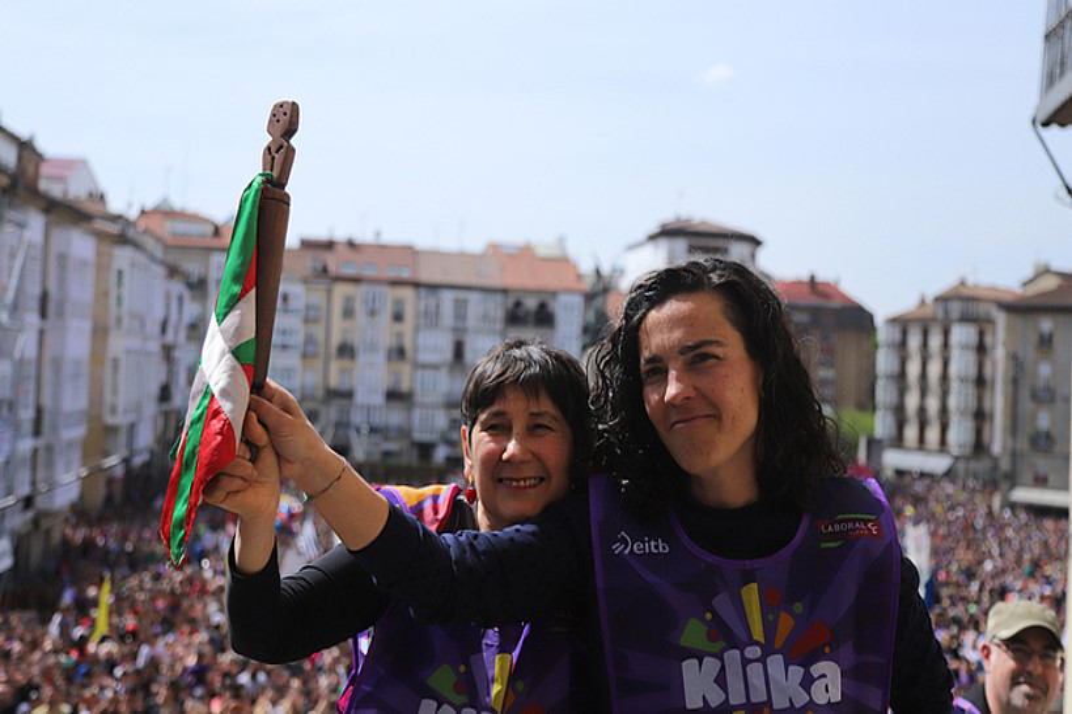 Maialen Lujanbio, mezuaren egilea, AEK-ko koordinatzaile Mertxe Mugikarekin lekukoari heltzen, igandean, Andre Maria Zuriaren plazan.