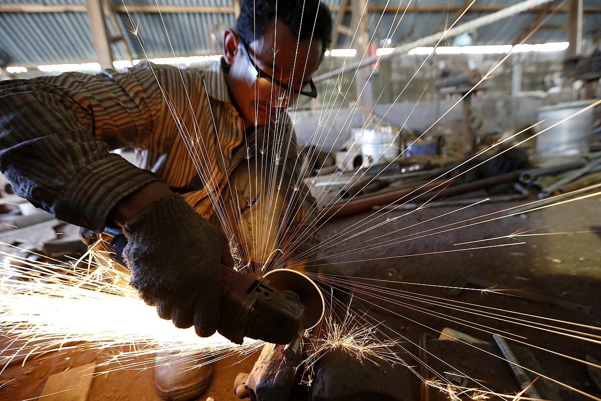 Behargin bat, metala mozten, babes eskasarekin, Indonesiako lantegi batean. ©HOTLI SIMANJUNTAK / EFE