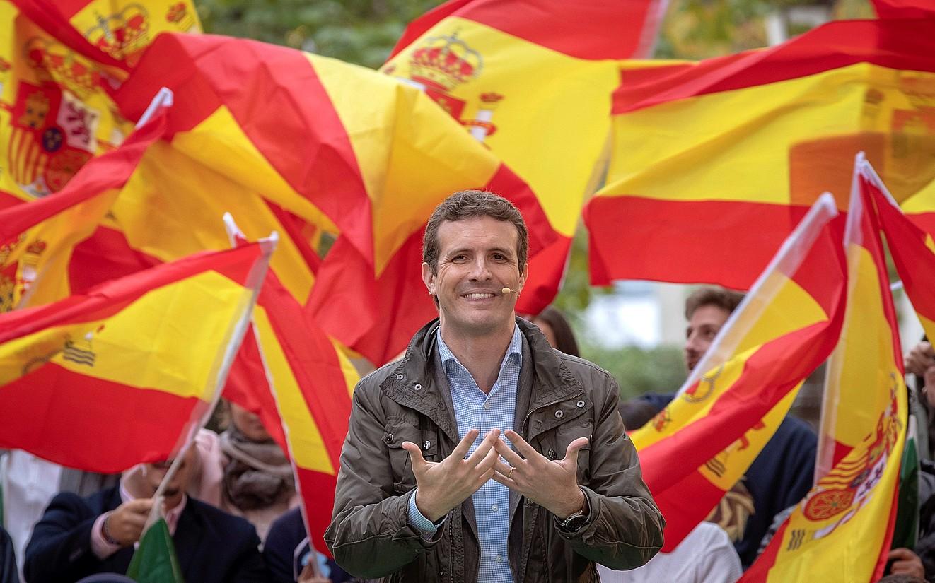 Pablo Casado, PPko presidentea eta hautagaia, kanpainako ekitaldi batean, banderaz inguratuta. / JULIO MUÑOZ / EFE
