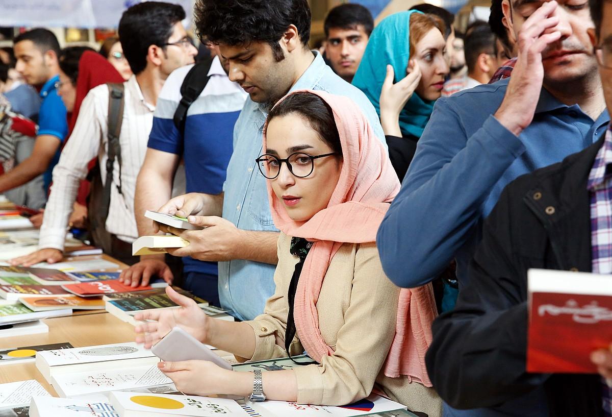 Zenbait gazte Teheranen, Liburuaren Nazioarteko Azokako erakusmahaietan dauden liburu batzuei begira. ©ABEDIN TAHERKENAREH / EFE