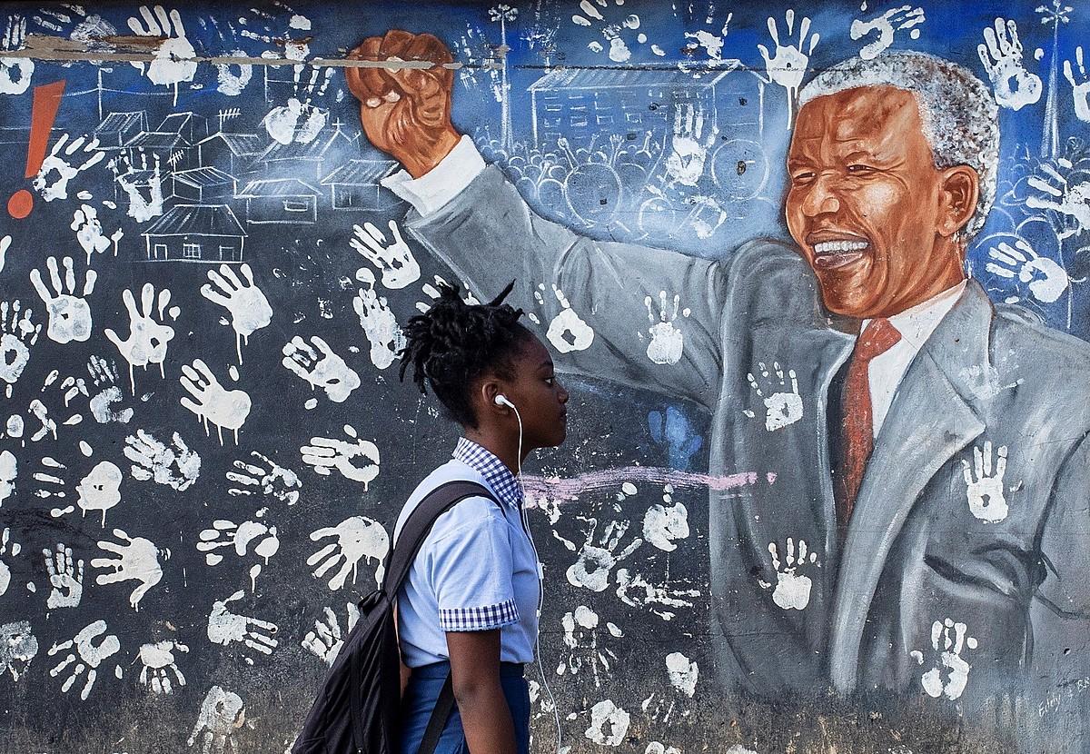 Ikasle bat atzo, Nelson Mandelaren mural baten aurretik pasatzen, Johannesburgon. ©KIM LUDBROOK / EFE