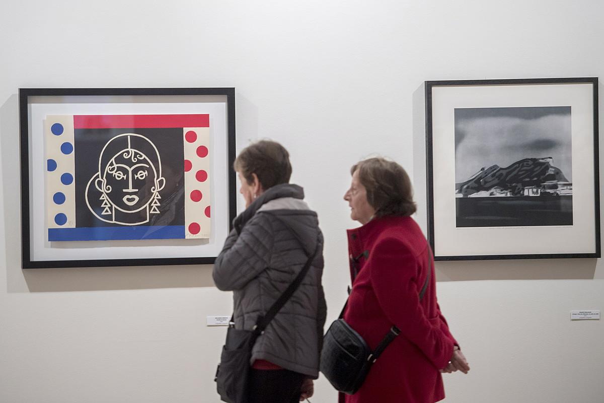 Bi bisitari Eduardo Arroyo artistaren <em>Waldorf Astoria</em> litografiari begira, Donostiako Okendo kultur etxeko erakusketan. ©JUAN CARLOS RUIZ / FOKU