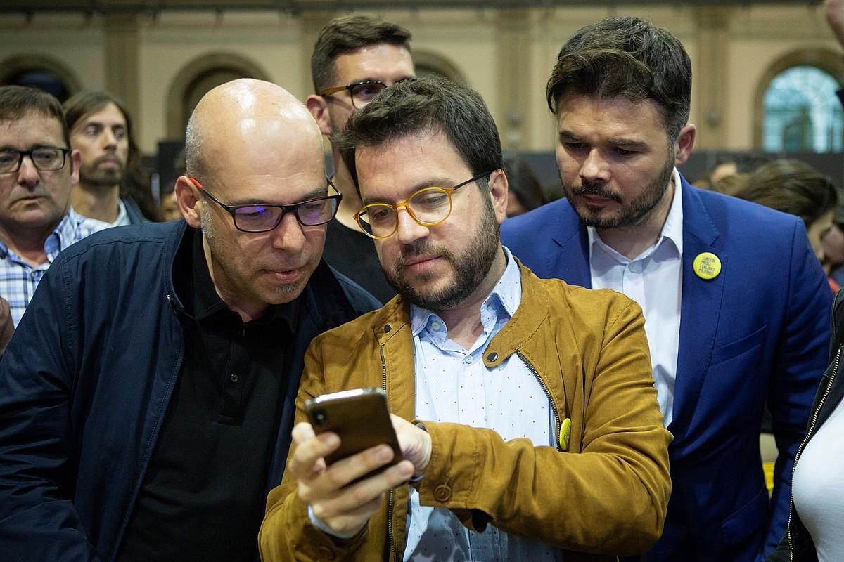 Pere Aragones Generalitateko presidenteordea (ERC) sakelakoari begira, atzean Gabriel Rufian duela. ©QUIQUE GARCIA / EFE