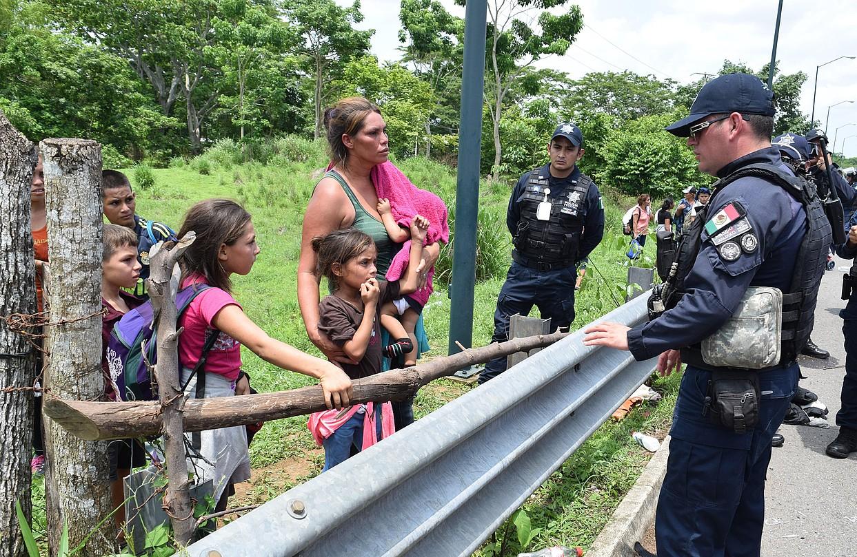 Erdialdeko Amerikako etorkin familia bateko kideak Mexikoko poliziekin hizketan, joan den ostegunean, Tapachula inguruan (Mexiko).
