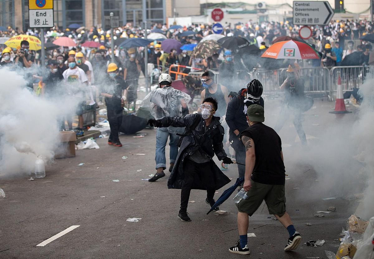 Kaskoekin, maskarekin eta aterkiekin babestu ziren hainbat manifestari, atzoko protestatan. ©JEROME FAVRE / EFE