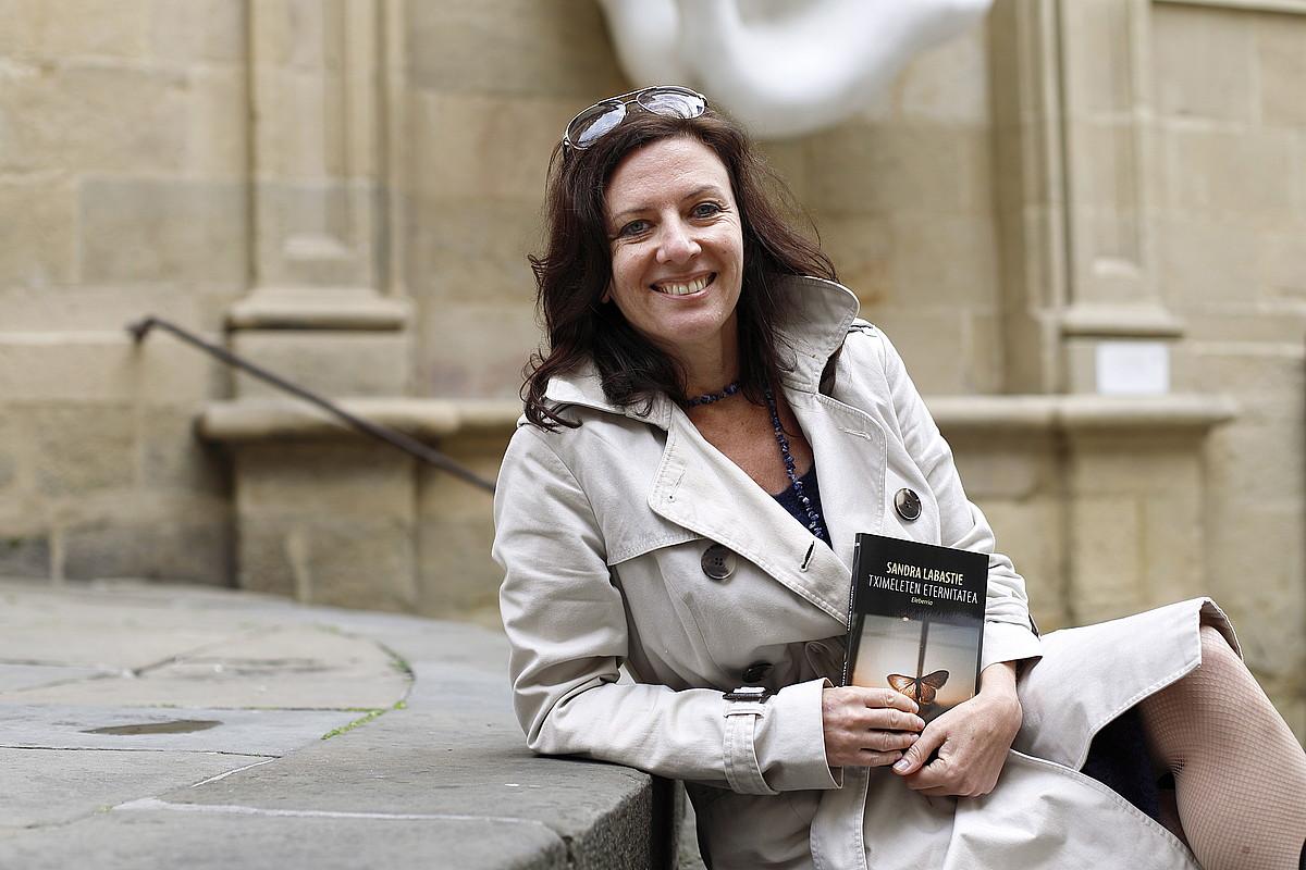 Sandra Labastie idazlea, Donostian, <em>Tximeleten eternitatea</em> (Alberdania) nobela eskuetan hartuta. ©MAIALEN ANDRES / FOKU