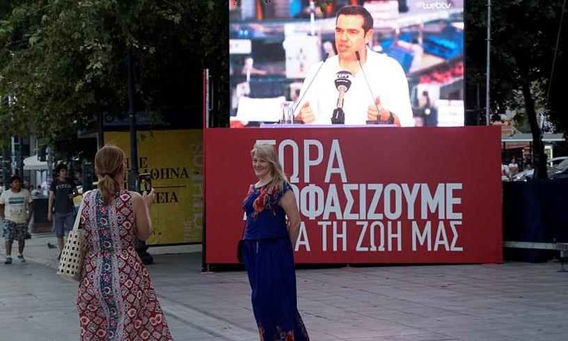 Emakume bat beste bati argazkia ateratzen, Atenasen, Tsiprasen mitin bat atzean dutela. ©E. P. VALLS / EFE