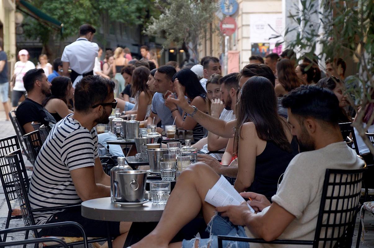 Gazte andana bat Atenas hiriburuaren erdiguneko terraza batzuetan. ©EMMA PONS VALLS / EFE