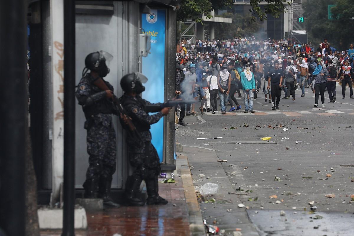 Oposizioaren jarraitzaileak eta Venezuelako segurtasun indarretako kideak borrokan, Caracasen, joan den urtarrilaren 23an. ©MIGUEL GUTIERREZ / EFE