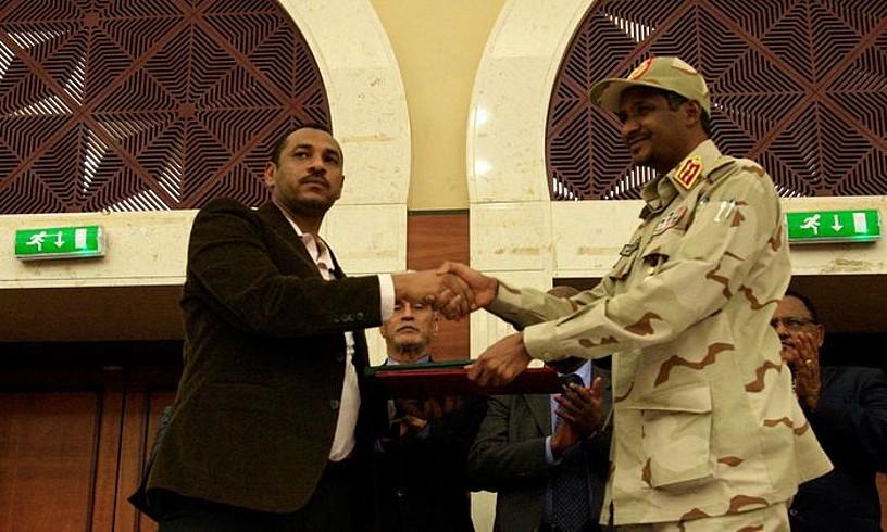 Ahmad al-Rabiah oposizioko buruetako bat eta Mohamed Hamdan Dagolo jenerala elkarri eskua ematen, atzo, Khartumen. ©EFE