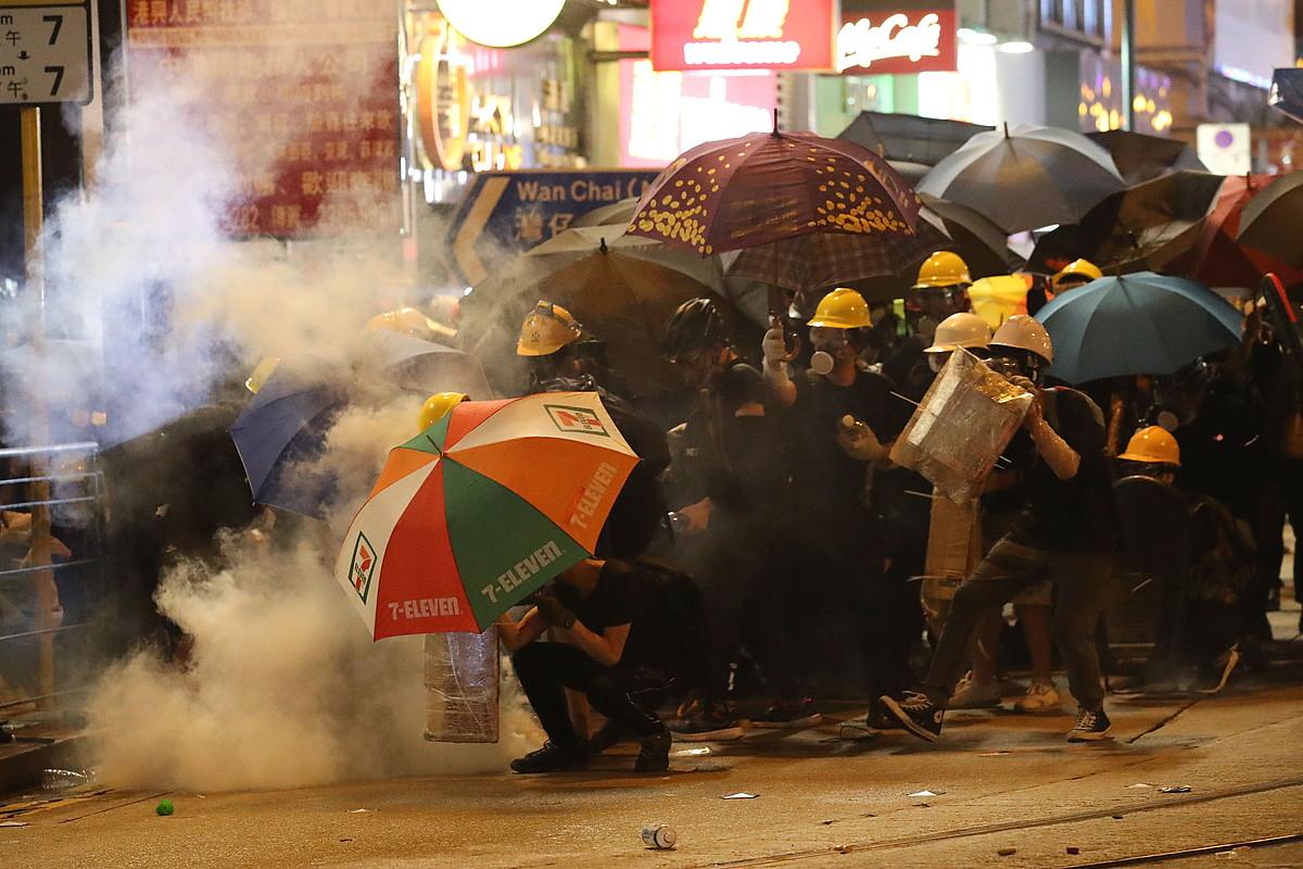 Manifestariak Poliziaren eraso batean defendatu nahian, herenegun Hong Kongen egindako protestan. ©RITCHIE B. TONGO / EFE