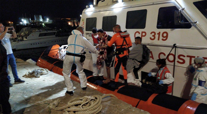 <em>Open Arms</em> erreskate ontzitik ebakuatutako lau migratzaileak, atzo, Lampedusako portura iristen. ©STR / EFE