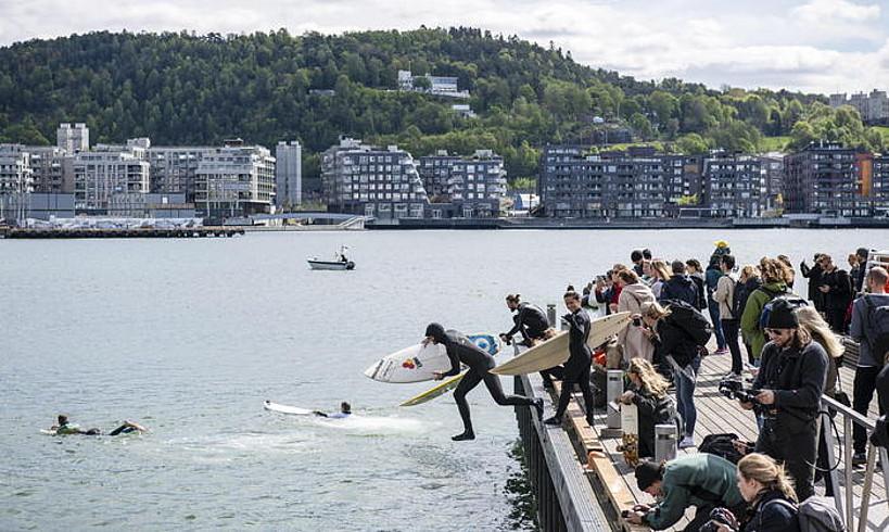 Hainbat herritar Osloko portuan, surf erakustaldi bat hastear dela.