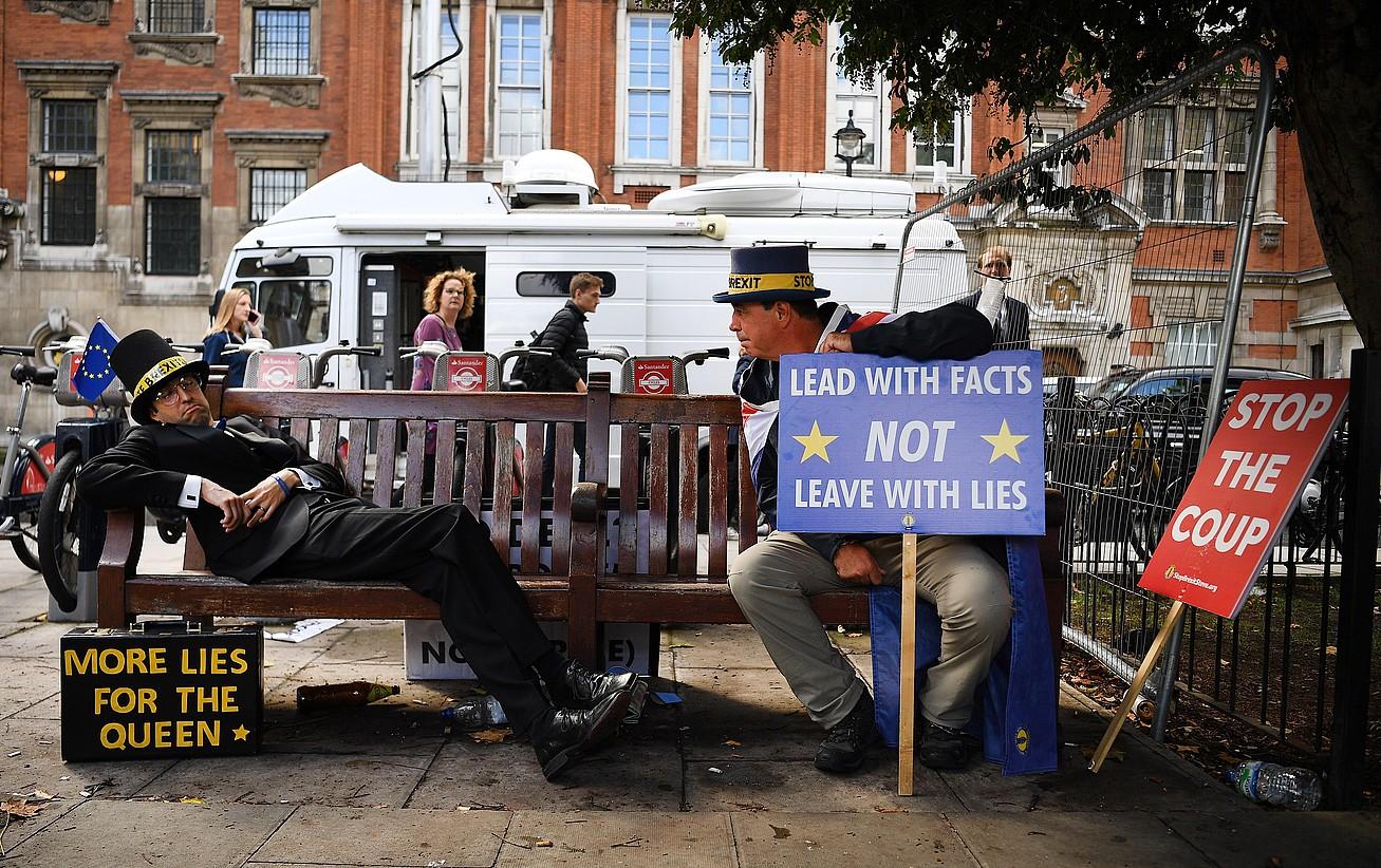 <em>Brexit</em>-aren aurkako manifestari bat —ezkerrekoa— Jacob Rees Mogg diputatu torya bezperan parlamentuko besaulkian etzan zeneko unea imitatzen, atzo, Londresen. ©ANDY RAIN / EFE
