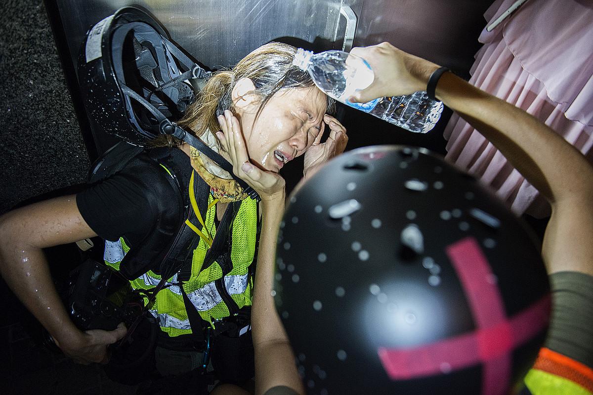 Poliziak begietara espraia jaurti dion kazetari bat, manifestari baten laguntza jasotzen. ©ZIGOR ALDAMA