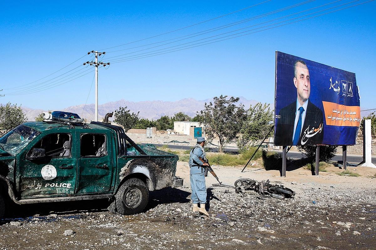 Polizia bat auto suntsitu baten ondoan, atzo, Txarikar hirian. Kartelekoa Amrullah Saleh da, Ganirekin presideorde izateko hautagaia. ©HEDAYATULLAH AMID / EFE