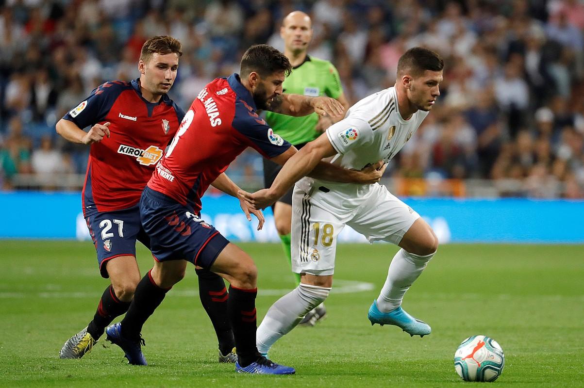 Raul Navas Osasunako atzelaria Luka Jovic Real Madrileko aurrelaria gerritik heltzen, atzoko partidako jokaldi batean. ©JUANJO MARTIN / EFE
