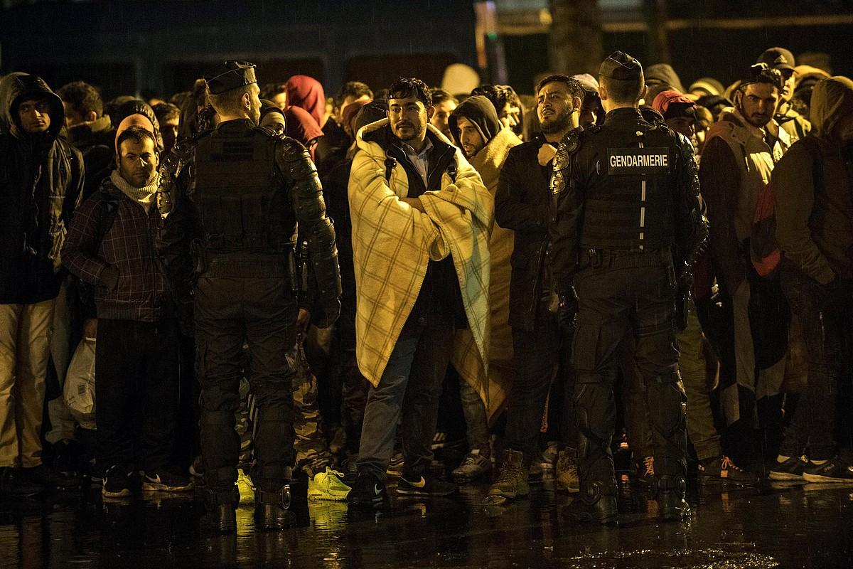 Migratzaileetako batzuk, jendarmeak parean dituztela, atzo goizaldean, Parisen. Ile-de-France eskualdeko hamabost gimnasiotara eraman zituzten. ©J. DE ROSA / EFE