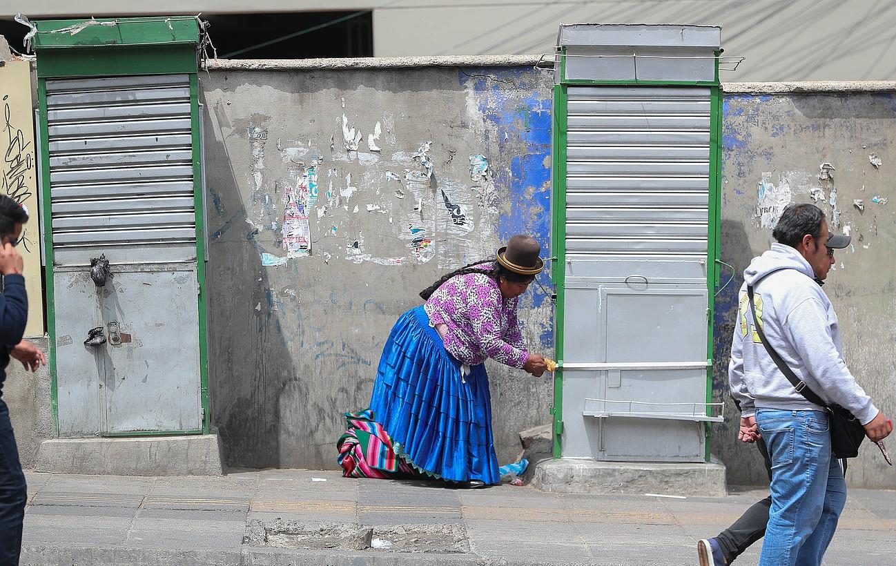 Emakume aimara bat bere salmenta gunea ixten, atzo, La Pazen. Istiluak hasi zirenetik zortzi lagun hil dira. ©MARTIN ALIPAZ / EFE