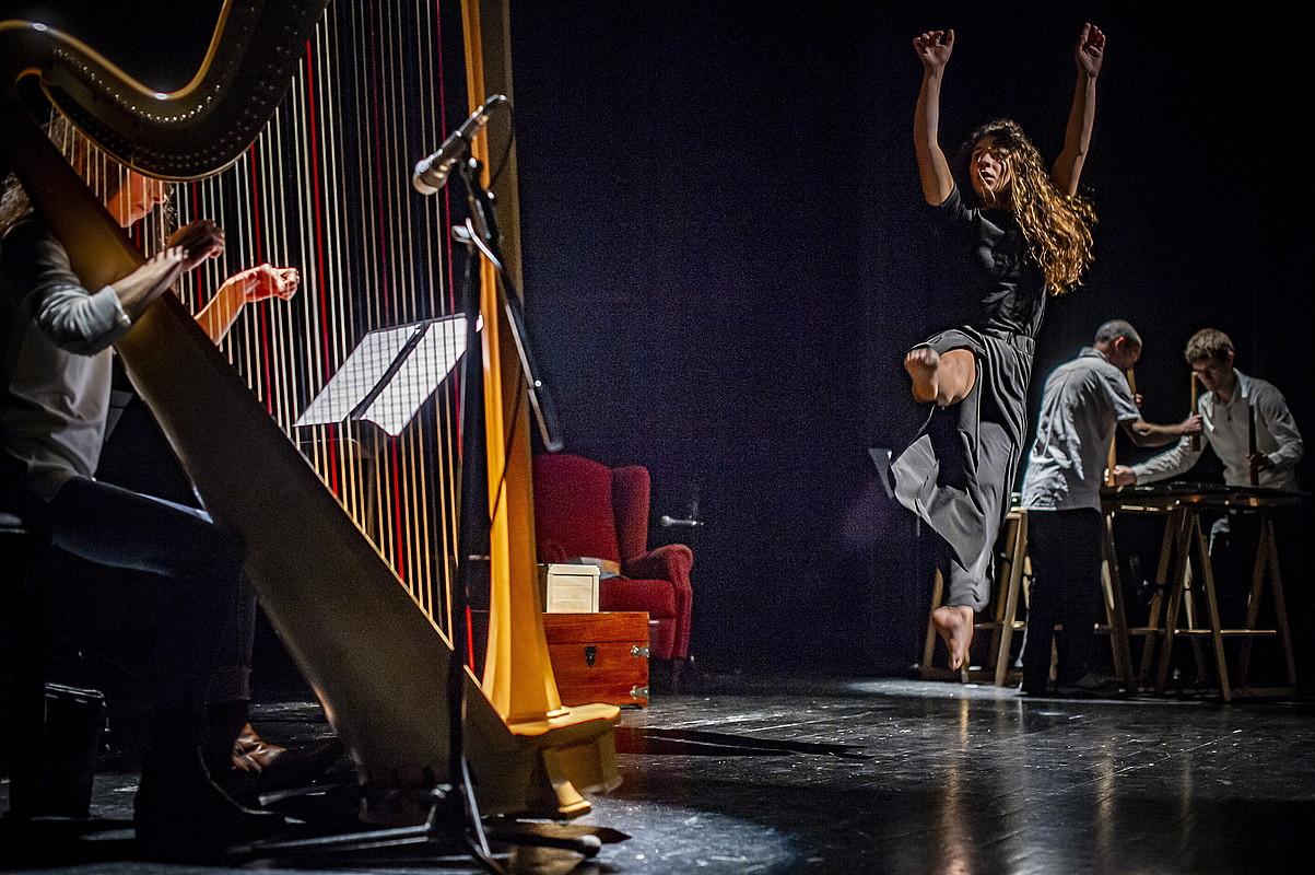 Maddi Argote dantzaria jauzi egiten, 'Gutun mezulariak' ikuskizunean. Haren aurrean, Ane Artetxe harpa jotzailea, eta atzean Kimu txalapartari bikotea. ©JAIZKI FONTANEDA / FOKU
