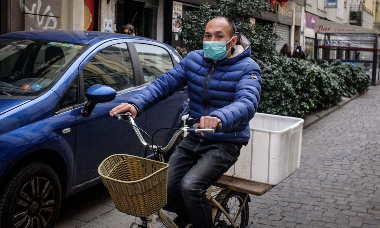 Txirrindulari bat atzo Milanen, ahoa estalia duela babesgarri batekin. ©MATTEO CORNER / EFE