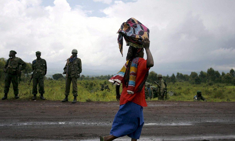 Emakume bat soldadu talde baten aurretik igarotzen, Kongoko Errepublika Demokratikoan. ©STEPHEN MORRISON /EFE