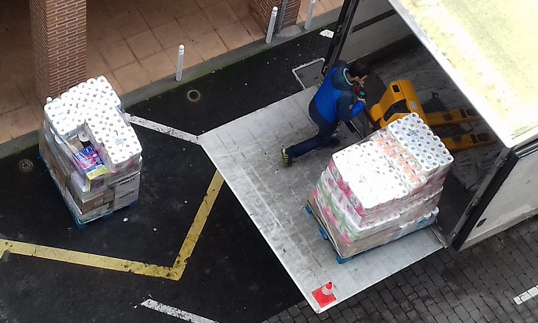 Atzoko bi irudi: ezkerrean, kamioi batetik komuneko papera jaisten, Azpeitian; eskuinean, komuneko paperaren paletak hutsik, Gipuzkoako saltoki batean. ©BERRIA