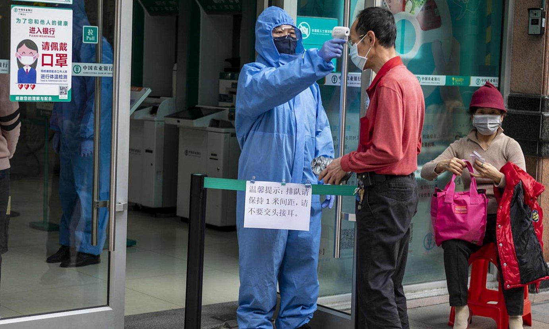 Segurtasun langile bat, herritar bati tenperatura hartzen, Guangzhou hiriko (Txina) banku baten sarreran, joan den otsailaren 24an. / ALEX PLAVEVSKI / EFE