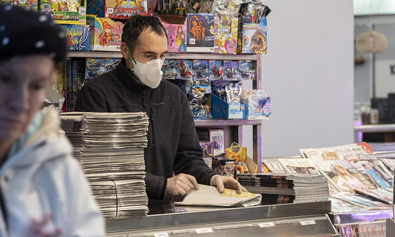 Saltzaile bat, maskara jarria duela, Donostiako San Martin merkataritza guneko kioskoan. / JON URBE / FOKU