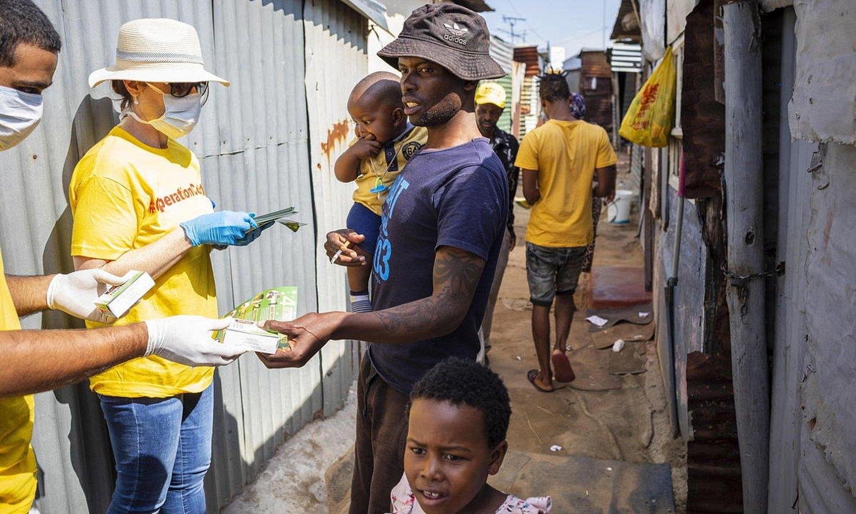Boluntarioak informazioa banatzen Johannesburgeko txabola auzo batean, Hegoafrikan. / KIM LUDBROOK / EFE