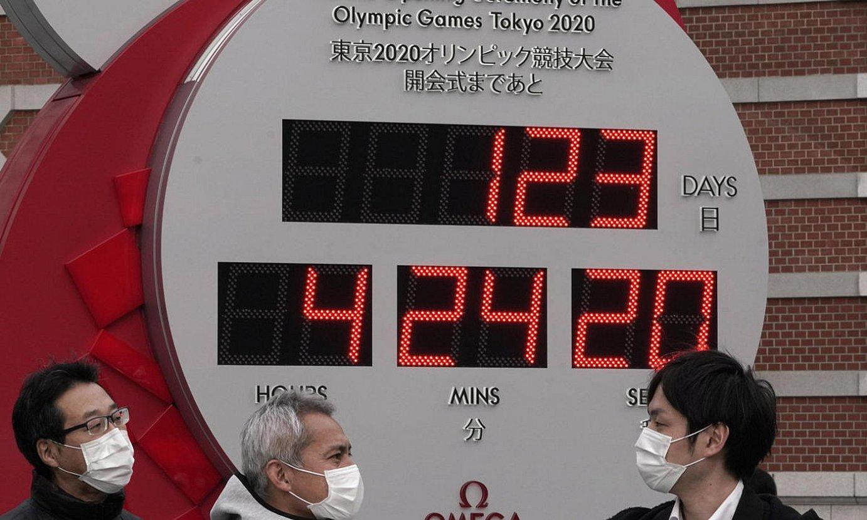 Olinpiar Jokoen atzerako kontua adierazten duen erlojua, maskarak dituzten pertsonaz inguratuta. ©KIMIMASA MAYAMA / EFE