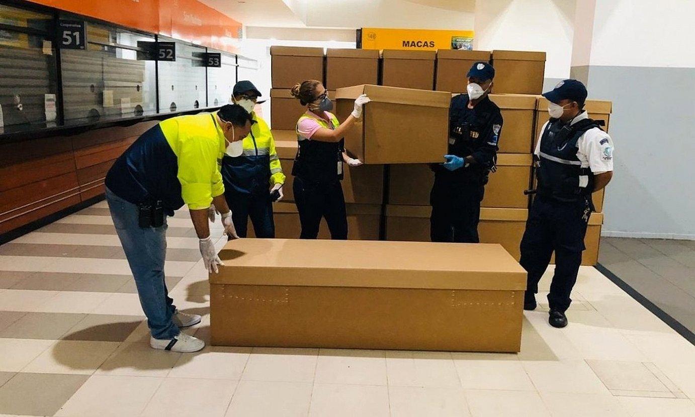 Langile talde bat kartoizko hil kutxak pilatzen, Ekuadorko Guayaquilen. / EFE