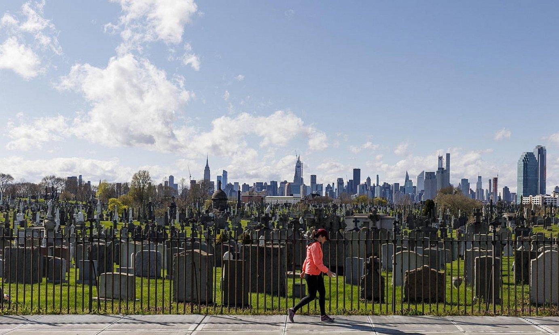 Emakumezko bat New Yorkeko Queens barrutiko Calvary hilerriaren ondoan paseatzen, joan den apirilaren 9an. / JUSTIN LANE / EFE