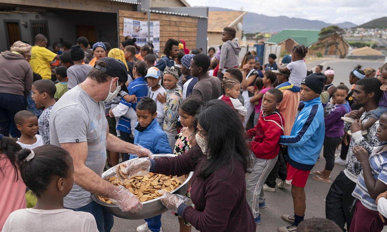 Boluntario bat Cape Towneko herritarren artean janaria banatzen, Hegoafrikan. ©NIC BOTHMA / EFE