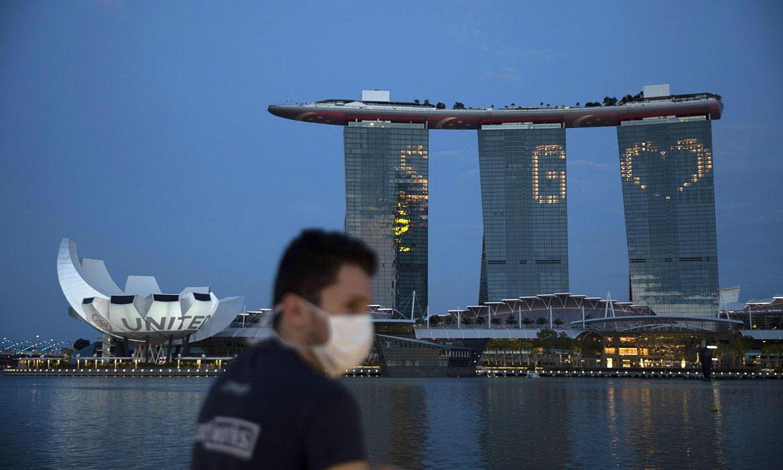 Gizon bat Singapurko Marina Bay Sands eraikinen parean paseatzen. / HOW HWEE YOUNG / EFE