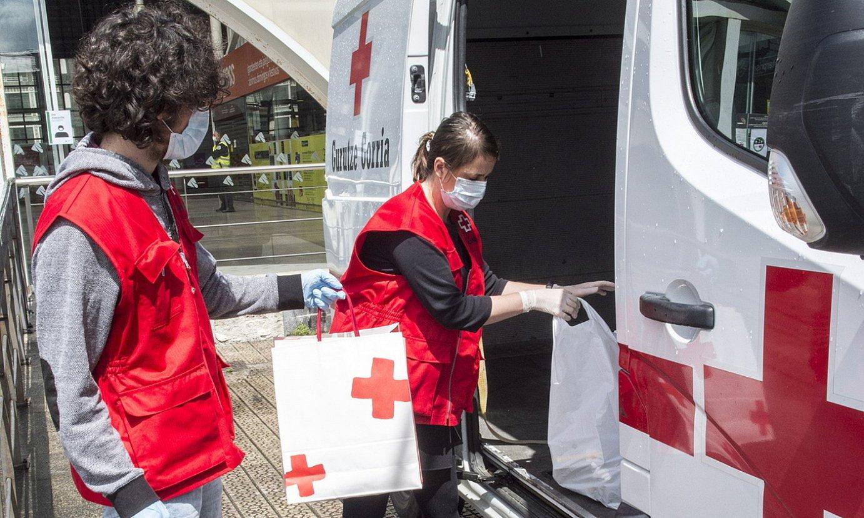 Gurutze Gorriko boluntarioak, poltsak furgonetan sartzen. / MARISOL RAMIREZ / FOKU