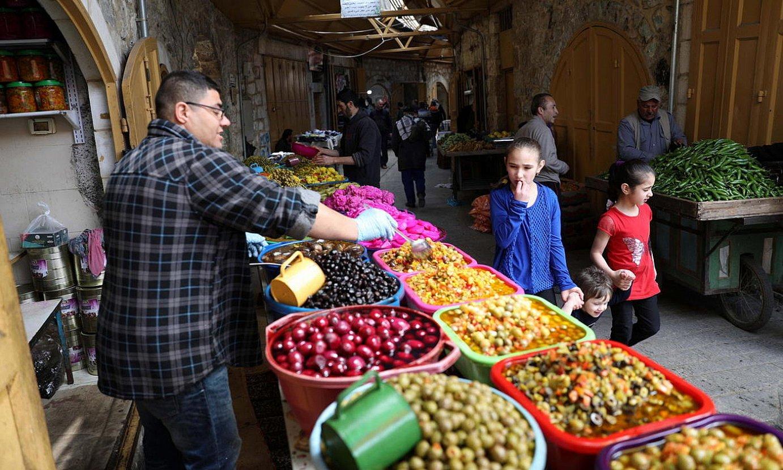 Gizon bat Zisjordania hegoaldeko Hebron hirian jakiak saltzen, iragan astean. ©ABED AL-HASHLAMOUN / EFE