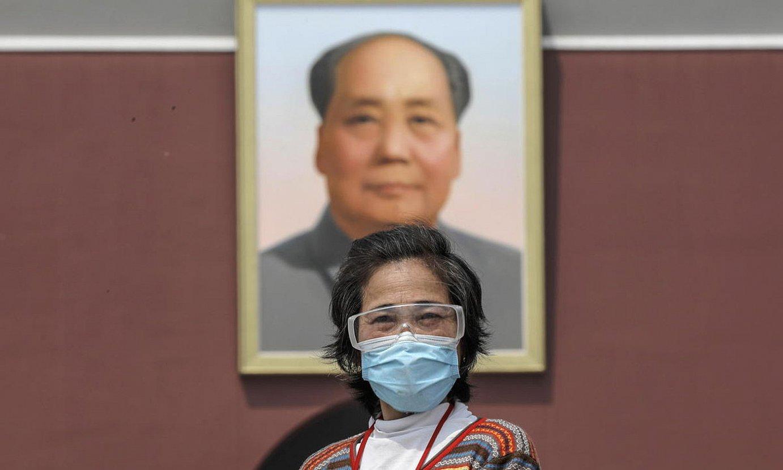 Turista bat Pekingo Tiananmen plazan, Mao Tse Tungen irudi erraldoiaren azpian. / WU HONG / EFE