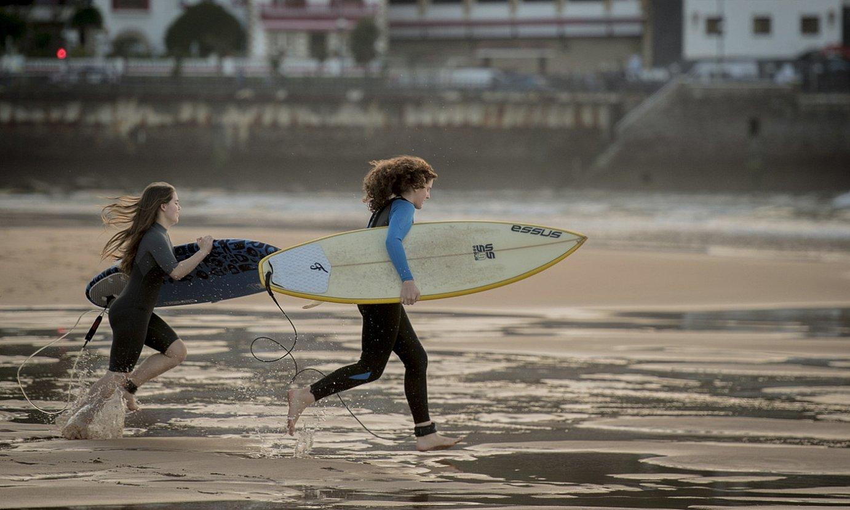 Bi surflari, lasterka, oholak besapean hartuta, Zarauzko hondartzan. ©GORKA RUBIO / FOKU