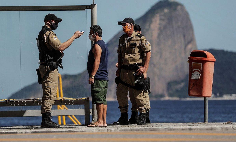 Segurtasun indarretako agenteak gizon bati tenperatura hartzen, Brasilen. / ANTONIO LACERDA / EFE
