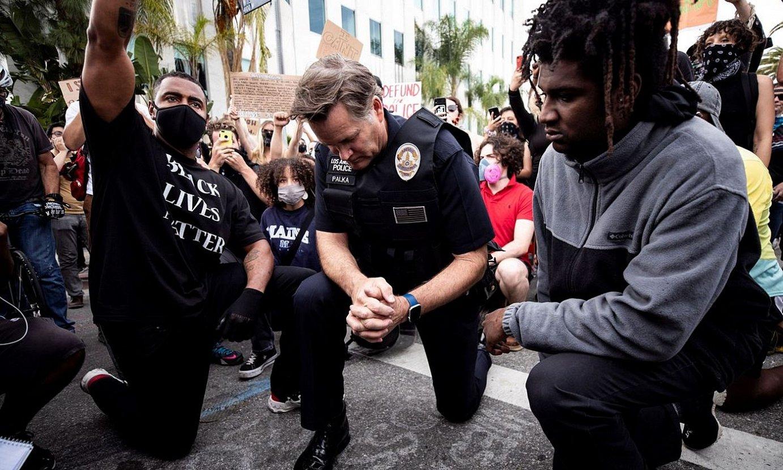 Los Angelesko Poliziako arduradun bat belauniko, manifestarien aldamenean, atzo. ©ETIENNE LAURENT / EFE