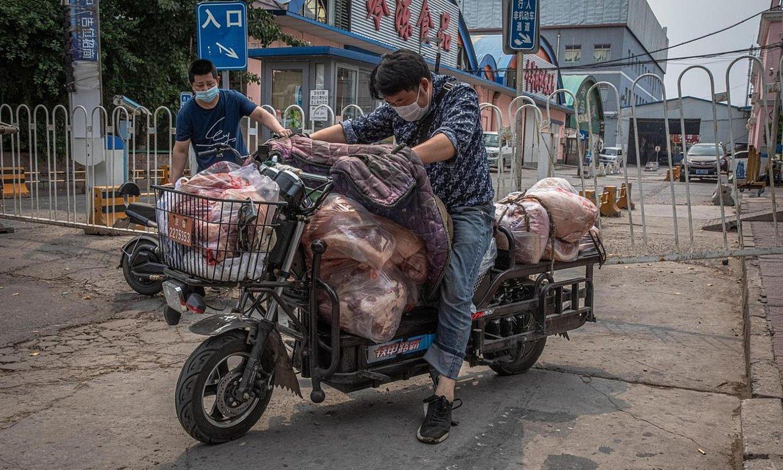 Bi gizon Xinfadiko merkatutik haragia eramaten. ©ROMAN PILIPEY / EFE