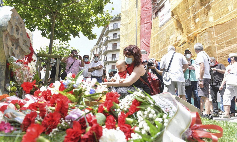 Ehunka pertsona bildu dira German Rodriguezen omenezko oroitarriaren inguruan, krabelinak uzteko.