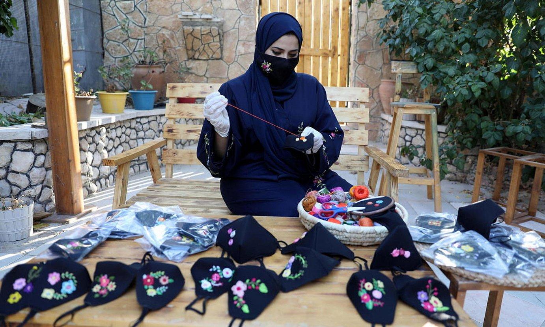 Emakume bat Zisjordaniako Bani Naim herrian maskarak saltzen, hil hasierako irudi batean. ©ABED AL HASHLAMOUN / EFE