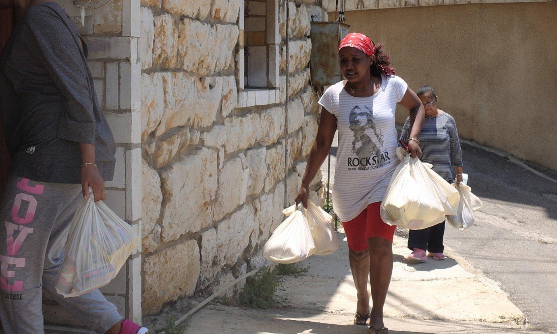 <b>Laguntza.</b> Sarah eta bere lankideak janaria banatzen, Beiruten. ©J. C. V.