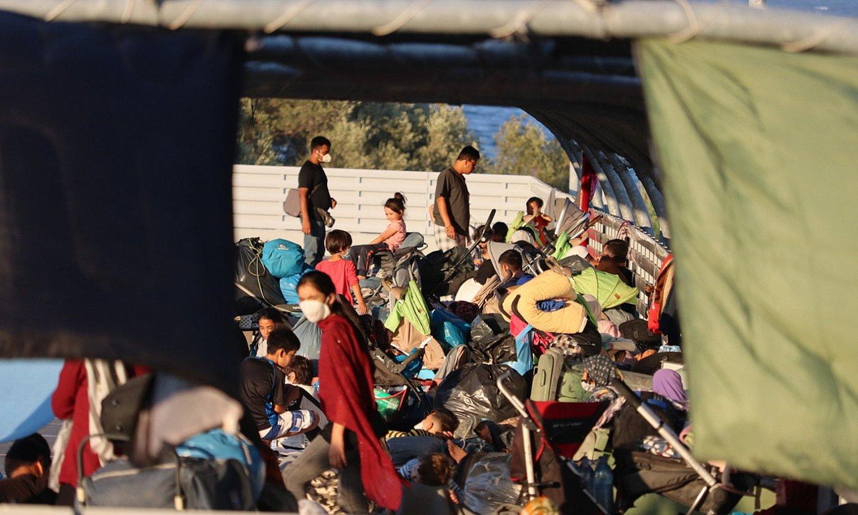 Migratzaile talde bat, kanpalekutik erreskatatutako gauzekin. ©IÑAKI AGIRRE