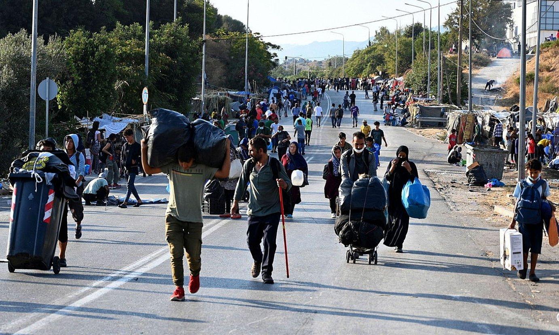 Migratzaileak kanpamentu berrira bidean. ©VANGELIS PAPANTONIS / EFE