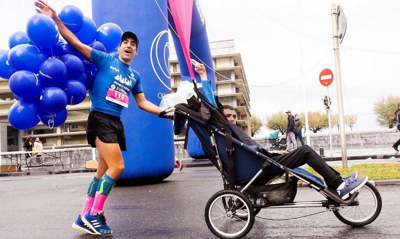 <b>Aefat elkartea. </b>Maratoilari solidario bat gurpil aulki bati bultzaka, Donostian. ©XAVIER D'ARQUER